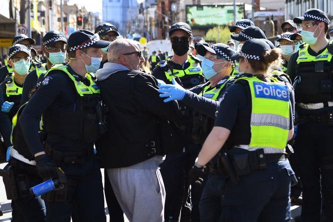 Des policiers retiennent un manifestant, samedi 18septembre, à Melbourne, en Australie.