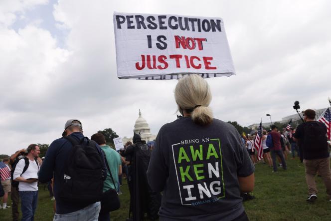 Protestujący podnosi tabliczkę z napisem