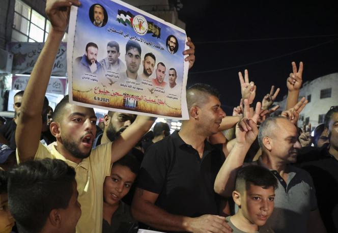Un Palestinien brandit un poster à l'effigie des six évadés d'une prison israélienne, dans le camp de Jénine, le 6 septembre 2021.