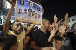 Un palestinien brandit un poster à l'effigie des 6 évadés d'une prison israélienne, dans le camp de Jenine, le 6 septembre 2021.