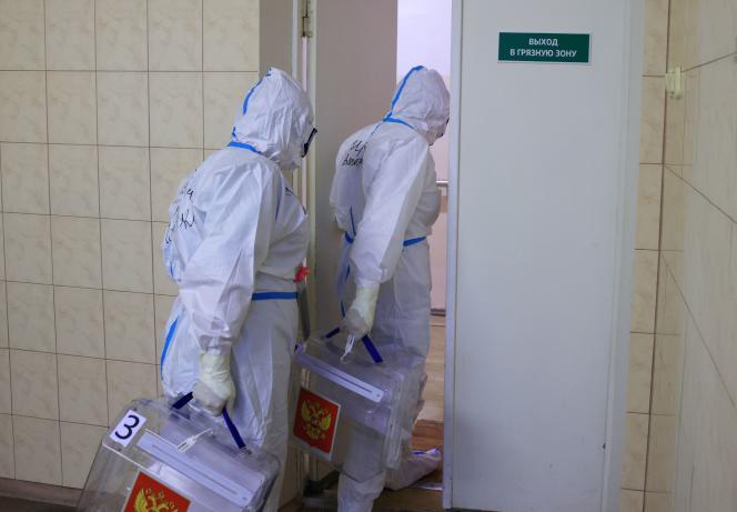 Des membres de la commission électorale, protégés, vont faire voter des malades du Covid-19, à Tver, en Russie, le 19 septembre 2021.