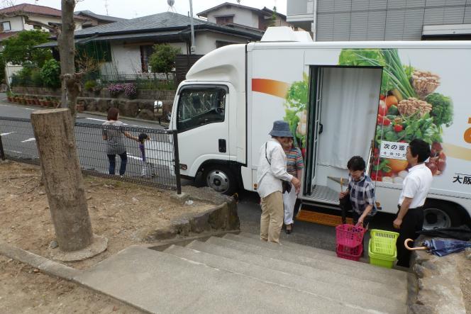 A Kawachinagano, à 25 km au sud-est d'Osaka, le passage du magasin ambulant géré par le supermarché avec le soutien de la mairie donne à plusieurs retraités l'occasion de converser avec des plus jeunes.