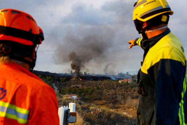 A member of civil protection and a forest firefighter watch a house burn due to lava from a volcano eruption in Cumbre Vieja National Park on September 20, 2021.