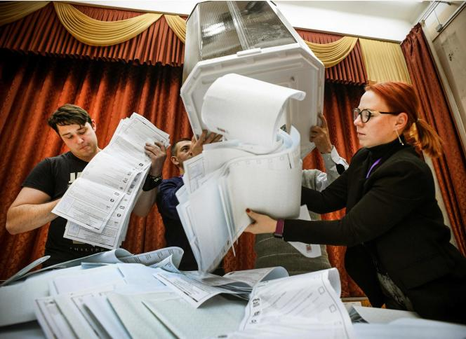 Members of a local election commission empty a ballot box at a polling station after the last day of parliamentary elections in Moscow on September 19, 2021.