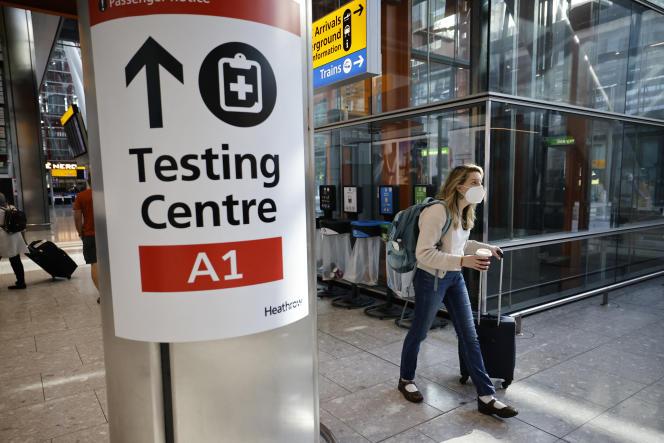 A l'aéroport londonien d'Heathrow, une affiche dirige les passagers vers un centre de dépistage du Covid-19, le 2 août 2021.