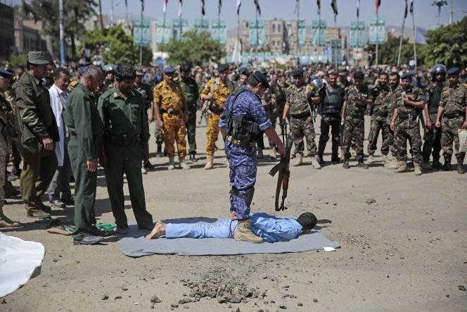 Un soldat se tient au-dessus d'un homme reconnu coupable d'implication dans le meurtre d'un haut responsable houthi en 2018. Place Tahrir à Sanaa, au Yémen, le 18 septembre 2021,.