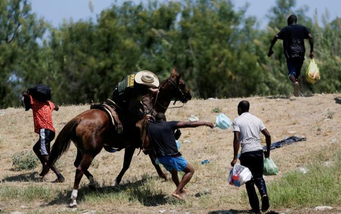 Un garde-frontière américain attrape un migrant par le tee-shirt, à la frontière américano-mexicaine, le 19 septembre 2021.