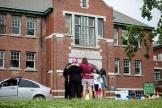 Une famille se recueille devant l'ancien pensionnat deKamloops, en Colombie britannique (Canada), le 3 juin 2021.