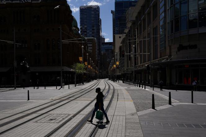 Un piéton traverse une rue vidée de ses passants, dans la ville confinée de Sydney, le 24 septembre 2021.