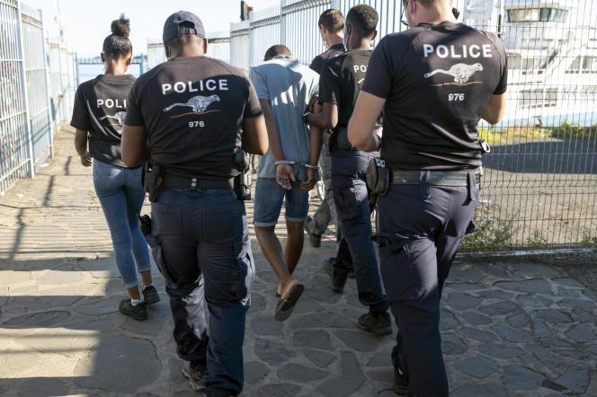 Des membres du Groupe d'appui opérationnel de la police aux frontièresescortent un homme n'ayant pas de papiers, à Mayotte, le 26 mars 2021.