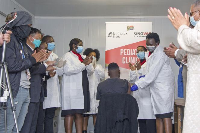 Applaudissements après l'administration du vaccin CoronaVac, de Sinovac, à un adolescent, à Pretoria (Afrique du Sud), le 12 septembre 2021.