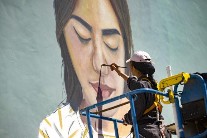 L'artiste marocaine Imane Droby travaille sur une fresque murale pendant le festival de street art Jidar dans la capitale Rabat, le 20 septembre 2021.