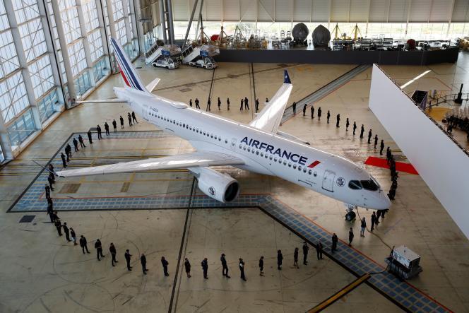 Des salariés d'Air France autour d'un Airbus A220 dans un hangar de l'aéroport de Roissy-Charles-de-Gaulle, à Roissy(Val-d'Oise), le 29 septembre 2021.