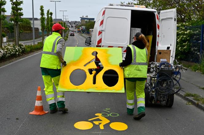 La «ville du quart d'heure» doit permettre de vivre en minimisant ses déplacements. Des employés municipaux utilisent des pochoirs pour marquer une ligne de circulation cycliste sur une route à Saint-Malo (Bretagne), le 11 mai 2020.