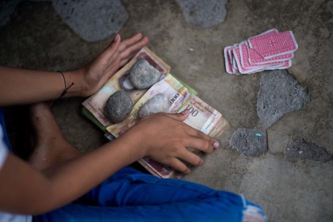Des enfants jouent aux cartes et parient avec des billets de bolivar vénézuélien inutilisés dans la ville de Puerto Concha, au Venezuela, le 9 septembre 2021.