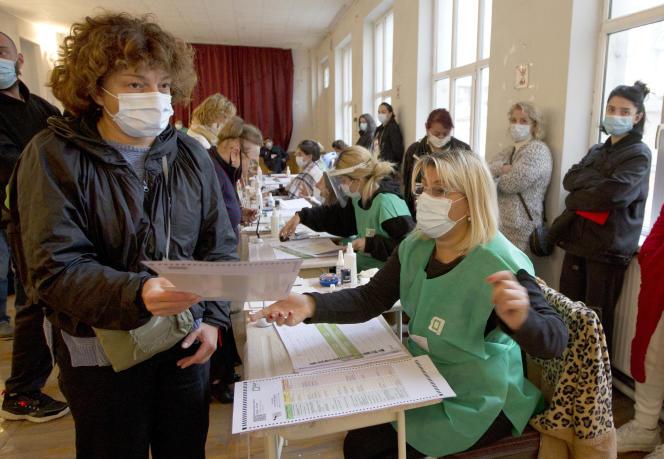 Seorang wanita mengulurkan kertas suaranya selama pemilihan kota 2 Oktober di Tbilisi.