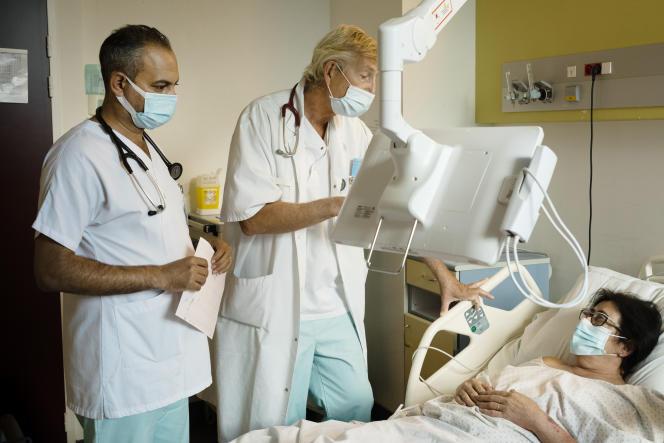 Géry Hannebicque, chef du service de cardiologie du centre hospitalier d'Arras, rend visite une patiente accompagné de Rida Chnider, stagiaire.