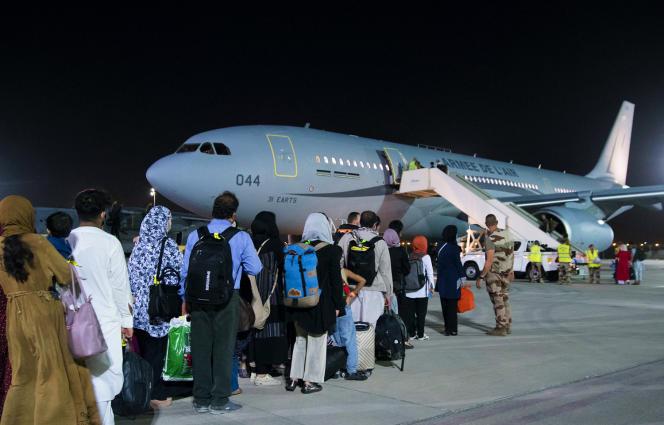 Des réfugiés afghans embarquent à bord d'un Airbus de l'Armée de l'air française lors d'une escale aux Emirats arabes unis, le 23 août.