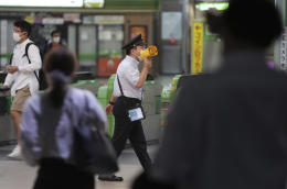 A station staff announces the restoration of train services at Shinjuku Station after a strong earthquake hit metropolitan area Thursday, Oct. 7, 2021, in Tokyo. (AP Photo/Eugene Hoshiko)