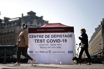 (FILES) This file photo taken on March 31, 2021 shows people walking past a tent where patients undergo an antigenic coronavirus test, at the Opera square in Paris amid the spread of the COVID-19 pandemic. As of October 15, Covid-19 tests will no longer be repay except on medical grounds or for those who have been vaccinated. (Photo by Thomas COEX / AFP)