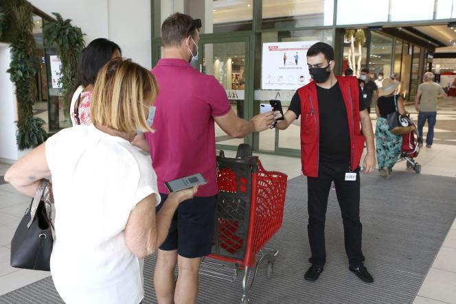 Un employé de supermarché vérifie le passe sanitaire de clients, à Ajaccio (Corse), le 16 août 2021.