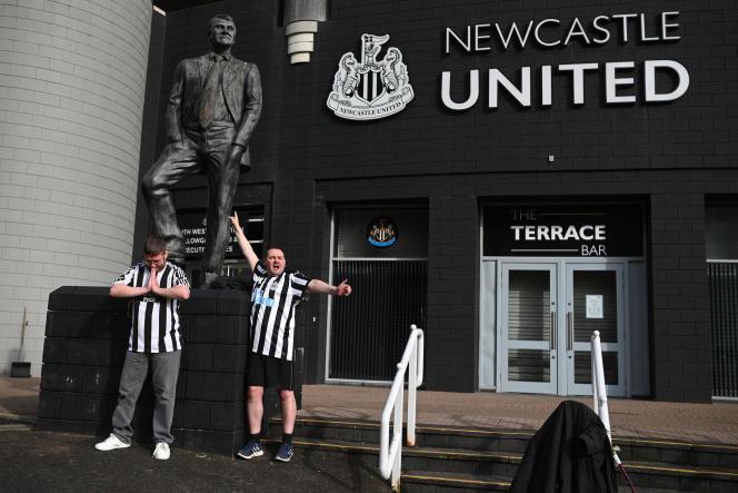 Des supporteurs de Newcastle United posent avec la statue de l'ancien manageur Bobby Robson devant le stade du club, à St James' Park, à Newcastle-upon-Tyne, dans le nord-est de l'Angleterre, le 8 octobre 2021.