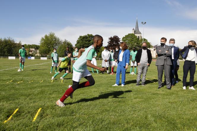 Emmanuel Macron rencontre des enfants s'entraînant au stade municipal lors d'une visite pour marquer la réouverture d'activités et d'installations sportives après des fermetures pendant la pandémie de Covid-19, à Pont-Saint-Marie (Aube), le 19 mai 2021.