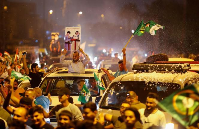 Des partisans irakiens du mouvement de Moqtada Al-Sadr célèbrent les résultats préliminaires de l'élection parlementaire irakienne à Bagdad, le 11 octobre 2021.