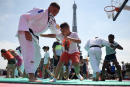 A young boy takes part in a Judo training session during the opening ceremony of the Tokyo 2020 Olympic Games at the fan village of the Trocadero, in front of the Eiffel Tower, in Paris, on July 23, 2021. (Photo by Lucas BARIOULET / AFP)