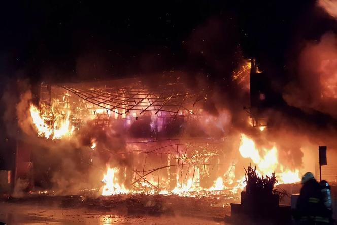 Foto de bombeiros em Kaohsiung, Taiwan, mostrando o prédio em chamas, 14 de outubro de 2021
