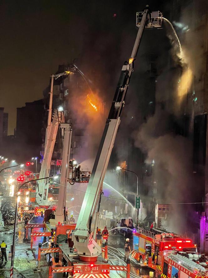 Quinta-feira, 14 de outubro de 2021 Bombeiros intervêm em frente a um prédio em chamas em Taiwan.