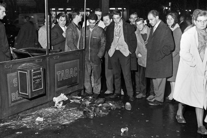 Des passants regardent des chaussures de manifestants abandonnées près d'un grand magasin lors de la manifestation pacifique organisée à Paris le 17 octobre 1961 par la fédération de France du FLN pour protester contre le couvre-feu imposé aux Français musulmans.