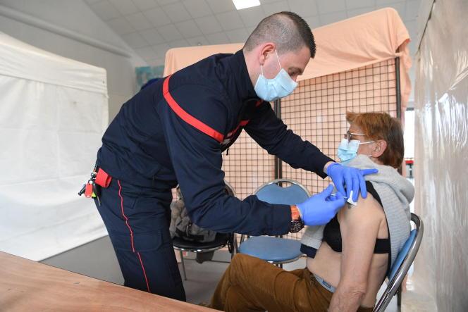 Un pompier du service départemental d'incendie et de secours (SDIS) vaccine un patient sur l'île d'Ouessant, le 19 mars 2021.