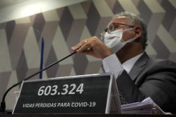 Une plaque indique le nombre de morts du Covid-19, devant le rapporteur de la commission d'enquête parlementaire, à Brasilia, le 18 octobre 2021.