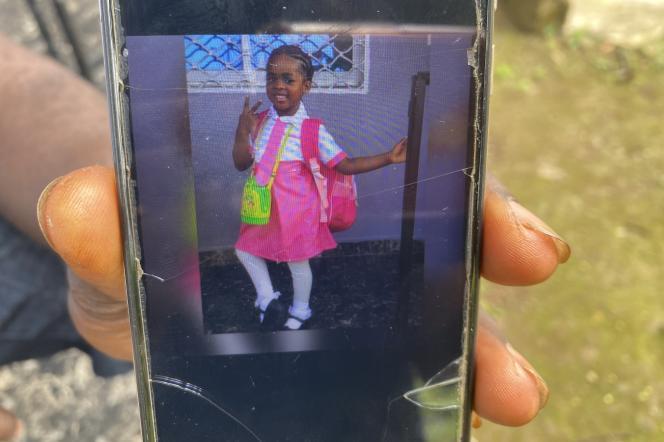 Edmond Ntungwe, oncle paternel de Caroluise Enondiale, montre un photo de la fillette sur son téléphone portable.