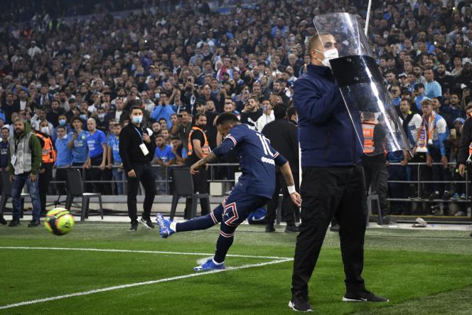 Neymar tire un corner protégé par le bouclier d'un membre du personnel de sécurité du Stade-Vélodrome, à Marseille, le 24 octobre 2021.