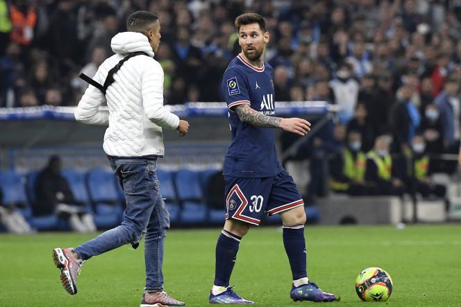 Lionel Messi est gêné par un supporteur entré sur le pelouse du Vélodrome lors du match Marseille-PSG, le 24 octobre 2021.