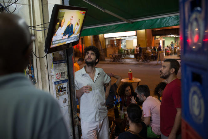 Brazilians gathered around a television broadcasting a video of Jair Bolsonaro published on the Internet, in a bar in the Lapa district, in Rio de Janeiro (Brazil), in October 2018.