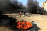 Des manifestants soudanais brûlent des pneus pour bloquer une route dans la 60ème rue de Khartoum, le 25 octobre 2021.