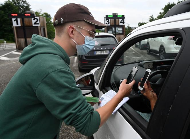 An employee checks a visitor's health pass behind the wheel of his car at the entrance to the Peaugres Safari Park (Ardèche), in July 2021.