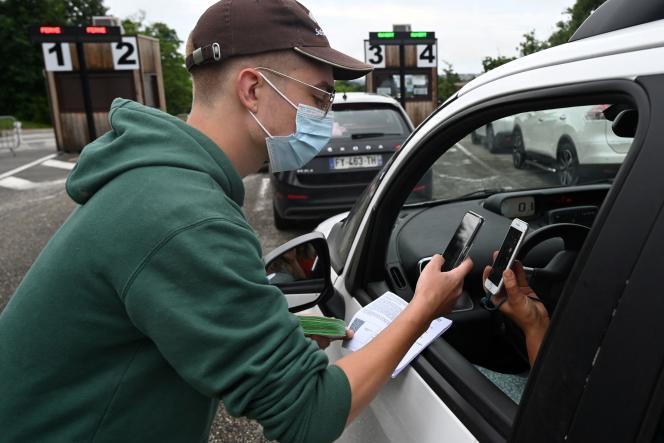 Un employé vérifie le passe sanitaire d'un visiteur au volant de sa voiture à l'entrée du parc safari de Peaugres (Ardèche), en juillet 2021.