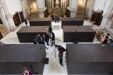 A general view of the Chinese artist Ai Weiwei six iron boxes part of a work presented as collateral event and shown during a press preview of the 55th edition of the Venice Biennale of Arts in Venice, northern Italy, Tuesday, May 28, 2013. The work on display is called S.A.C.R.E.D. The four initials standing for supper, accuser, cleansing, ritual, entropy and doubt, and referring to Ai Weiwei time 81 days in detention in 2011. Chinese artist Ai Weiwei has been prevented by Chinese authorities from traveling to Venice for the opening of two new works on the sidelines of the Biennale contemporary art show, so his mother came instead. Weiwei's elderly mother, Gao Yng, on Tuesday viewed for the first time a series of dioramas depicting six episodes of pressure during her son's 81 days in detention in 2011. (AP Photo/Domenico Stinellis)