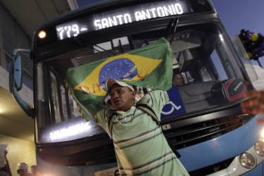 A man holding a Brazilian national flag stands in front of a bus during a protest demanding improvements be made to the public transport system, at the bus station in the centre of Brasilia June 19, 2013. This month's transport fare hikes, which came as Brazil struggles with annual inflation of 6.5 percent, stirred a groundswell of other complaints, leading to the biggest protests to sweep Brazil in more than two decades.   REUTERS/Ueslei Marcelino (BRAZIL - Tags: POLITICS CIVIL UNREST TRANSPORT BUSINESS)