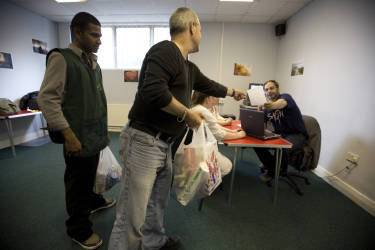 Volunteers handing over provisions bags at the Stoke Food Bank at the Hanley Baptist Church in Stoke-on-Trent, England. The food bank caters for about 50 people each week by supplying people with basic food items and was typical of many in existence in England during the recession. The UK government were to announce their latest spending round the following day, with many communities expected to face further hardship.