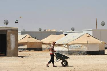 A young Syrian refugee pushes a wheelbarrow at Zaatari refugee camp, near the Jordanian city of Mafraq July 18, 2013. The refugee camp holds roughly 115,000 Syrian refugees in Jordan about 12 km (eight miles) from the Syrian border. REUTERS/Mandel Ngan/Pool (JORDAN - Tags: POLITICS SOCIETY IMMIGRATION)