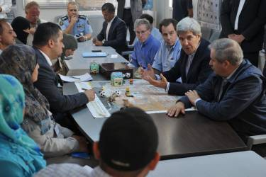 U.S. Secretary of State John Kerry (2nd R) greets a group of Syrian refugees during a joint meeting with Jordanian Foreign Minister Nasser Judeh (sitting, R) at the Zaatari refugee camp near the Jordanian city of Mafraq July 18, 2013. REUTERS/Mandel Ngan/Pool (JORDAN - Tags: POLITICS)