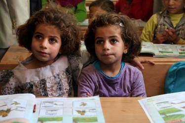 Twin sisters, who fled the fighting in Syria with their family, sit at their desks at the UNICEF school, during a visit by the Italian foreign minister, Emma Bonino to the Zaatari refugee camp near the Syrian border, in Mafraq, Jordan, Tuesday, June 25, 2013.  (AP Photo/Mohammad Hannon)