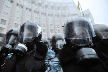 Riot police wear gas masks as they block protesters in front of Cabinet of Ministers of Ukraine during a rally in Kiev on November 24, 2013. Thousands of pro-Europe protesters in Ukraine attempted to storm the government building in the capital of Kiev Sunday, clashing with police who fired tear gas to keep them back. Protesters tried to break through police ranks surrounding the building, with some throwing stones and hitting officers with the signs they were carrying, as police fought back with batons, an AFP correspondent reported. AFP PHOTO / GENYA SAVILOV