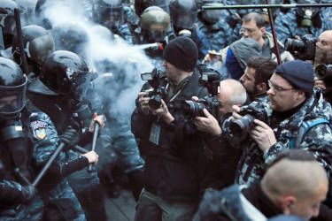 Photographers take photos during a fight between opposition protesters and riot police in front of the Ukrainian Cabinet of Ministers in Kiev, Ukraine, Sunday, Nov. 24, 2013. Tens of thousands of demonstrators demand that the Ukrainian government reverse course and sign a landmark agreement with the European Union in defiance of Russia. The protest was the biggest Ukraine has seen since the peaceful 2004 Orange Revolution, which overturned a fraudulent presidential election result and brought a Western-leaning government to power. (AP Photo/Efrem Lukatsky)