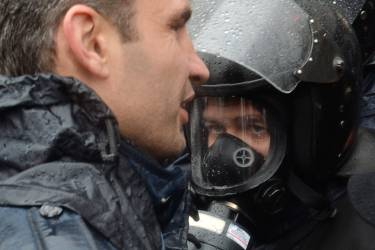 A riot policemen listens to world boxing champion and Ukrainian opposition UDAR (Punch) party leader Vitaliy Klitschko (L) outside the Ukrainian Cabinet of the Ministers during a protest in Kiev on November 25, 2013. Pro-West Ukrainians staged the biggest protest rally in Kiev since the 2004 Orange Revolution, demanding that the government sign a key pact with the European Union. The opposition called the rally after President Viktor Yanukovych's government reversed a plan to sign a historic deal deepening ties with the European Union, in a U-turn critics said was forced by the Kremlin. AFP PHOTO/ SERGEI SUPINSKY